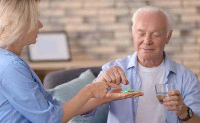 woman giving medicine to senior man at home