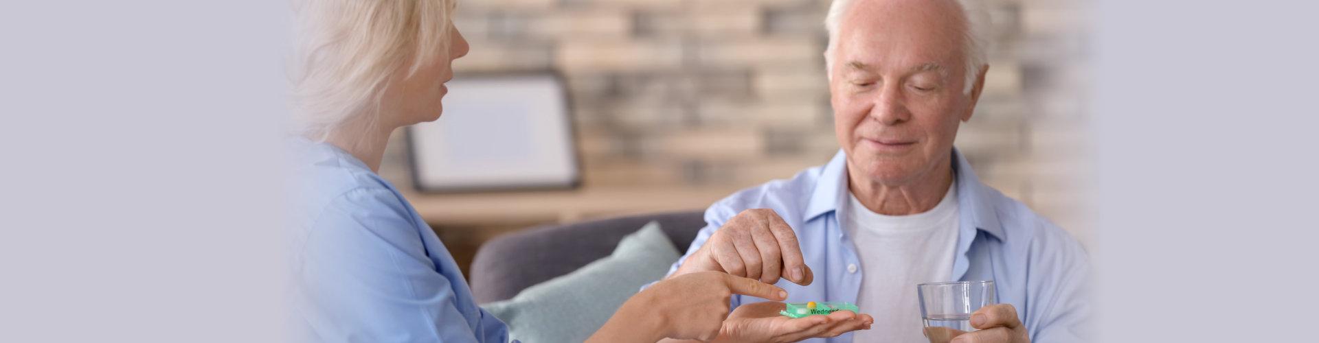 woman giving medicine to senior men at home